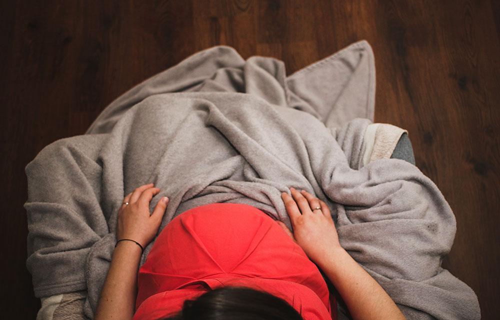 Herpes in der Schwangerschaft: Schwangere sitzt besorgt wegen Herpes auf einem Sessel unter einer Decke