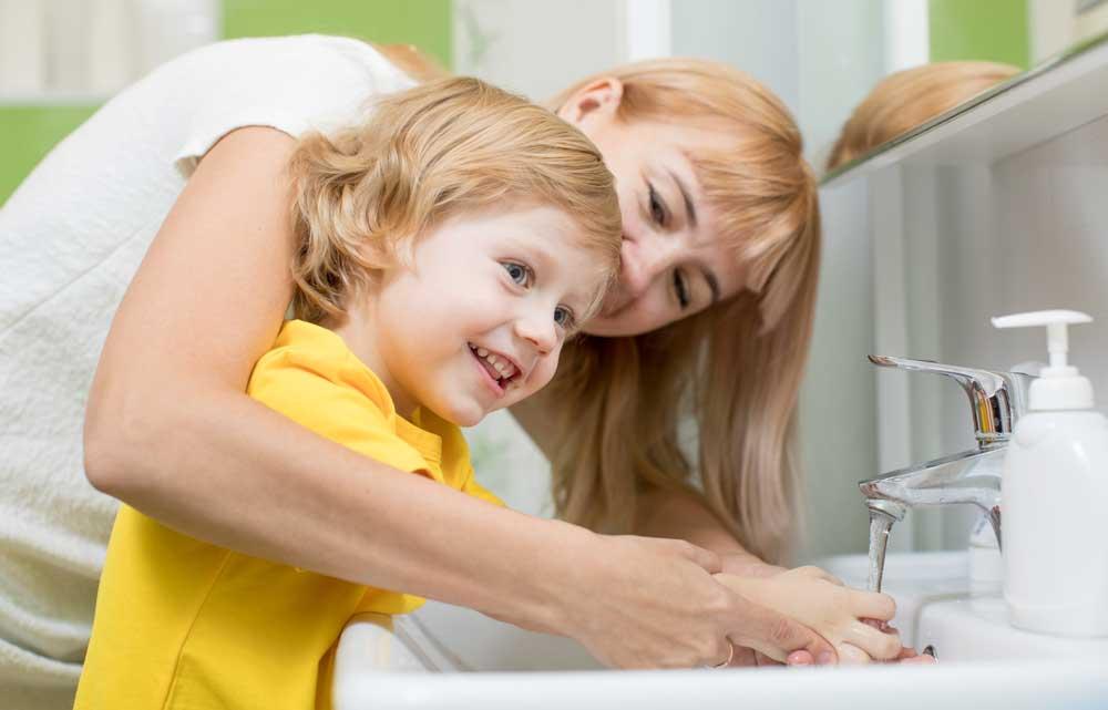 Handhygiene am Kind bei Herpes - Mutter wäscht Kind die Hände im Badezimmer